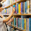 Woman pulling out a book from a shelf — Stock Photo