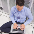 Stock Photo: Musing his laptop in datcenter