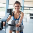 Smiling brunette training on row machine - Stock fotografie