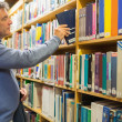 Stock Photo: Man taking a book from the shelves