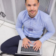 Stock Photo: Smiling musing laptop in front of servers