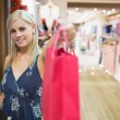 Smiling woman passing shopping bag - Foto Stock