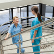 Two nurses standing opposite each other in stairwell — Stock Photo #23052562