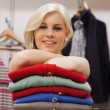 Woman leaning on clothes smling - Foto Stock