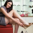 Woman is sitting in a boutique trying shoes — Stock Photo