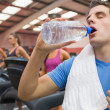 Man drinking water in the gym with towel around neck — Stock Photo