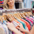 Woman standing at the clothes rack smiling - Stok fotoğraf