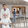 Doctor pushing a woman — Stockfoto
