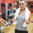 Stock Photo: Womwith towel around neck in weights room