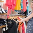 Woman standing at a clothes rail — Stock Photo