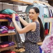 Woman putting jumpers on shelf — Stock Photo