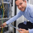 Technician plugging in cables and using tablet pc — Stockfoto