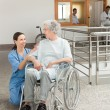 Nurse looking after old women sitting in wheelchair — Stock Photo #23052786