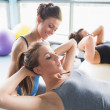 Female trainer helping woman doing sit-ups — Stock Photo #23052792