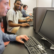 Smiling young man at computer class — Stock Photo