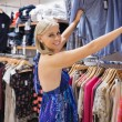 Woman looking through clothes and smiling - Stock Photo