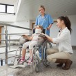 Mother crouching next to her child in wheelchair with nurse push — Stock Photo