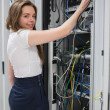 Smiling brunette fixing wires of server - Foto de Stock