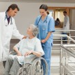 Nurse and doctor talking with old woman in wheelchair — Stock Photo