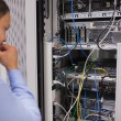Man looking at rack mounted servers — Stock Photo #23053202