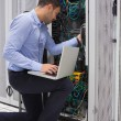 Man fixing wires while doing maintenance in data center — Stock Photo
