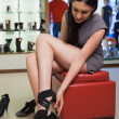 Stock Photo: Womsitting in boutique trying shoes