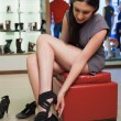 Womsitting in boutique trying shoes — Stock Photo #23053428
