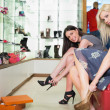 Women trying on shoes smiling — Stock Photo #23053436