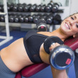 Smiling woman training with weights — Stock Photo #23053490