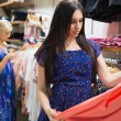 Woman is looking at clothes — Stockfoto