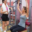 Woman talking to friend using weights machine - Stock fotografie