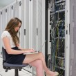 Woman working on laptop with servers — Stock Photo