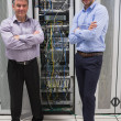 Two technicians standing in front of servers - Stock Photo