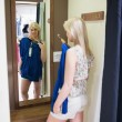 Woman standing in front of a mirror - Stock fotografie