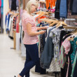 Woman searching for clothes standing in a shop - Stock fotografie