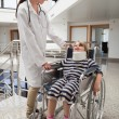 Female doctor smiling at child in wheelchair and neck brace — Stock Photo