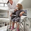 Doctor talking to child with neckb race in wheelchair — Foto de Stock