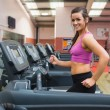 Stock Photo: Womrunning on treadmill in gym looking happy
