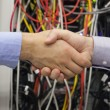 Hand shake in front of wires - Stockfoto