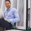 Stock Photo: Happy techniciworking on laptop connected to server