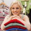 Woman is leaning on clothes and smiling - Stock Photo