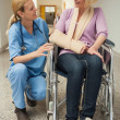 Stock Photo: Nurse talking with patient in wheelchair with arm in sling