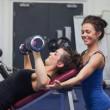 Stock Photo: Female trainer teaching womlifting weights