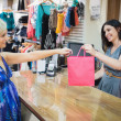 Woman handing over shopping bag at cash register - Stock Photo