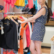 Woman is standing at a clothes rack smiling - 图库照片