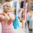 Woman smiling in clothes shop — Stock Photo
