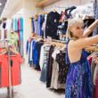 Foto Stock: Womlooking through clothes at boutique