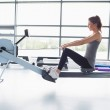 Woman working out on row machine — Stock Photo #23054444