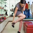 Stock Photo: Woman standing trying on shoes