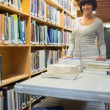 Stock Photo: Smiling librarian pushing book trolley